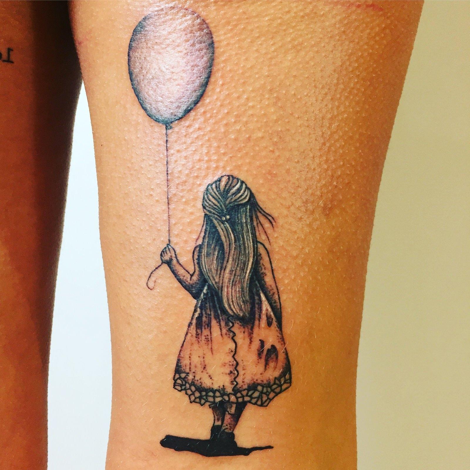 Tatuagem feminina de garota de costas segurando um balão