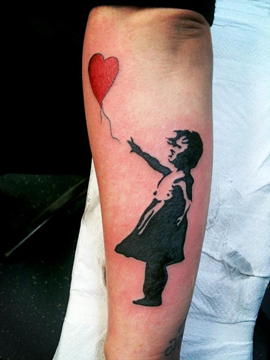 Tatuagem com menina segurando balão vermelho no formato de coração