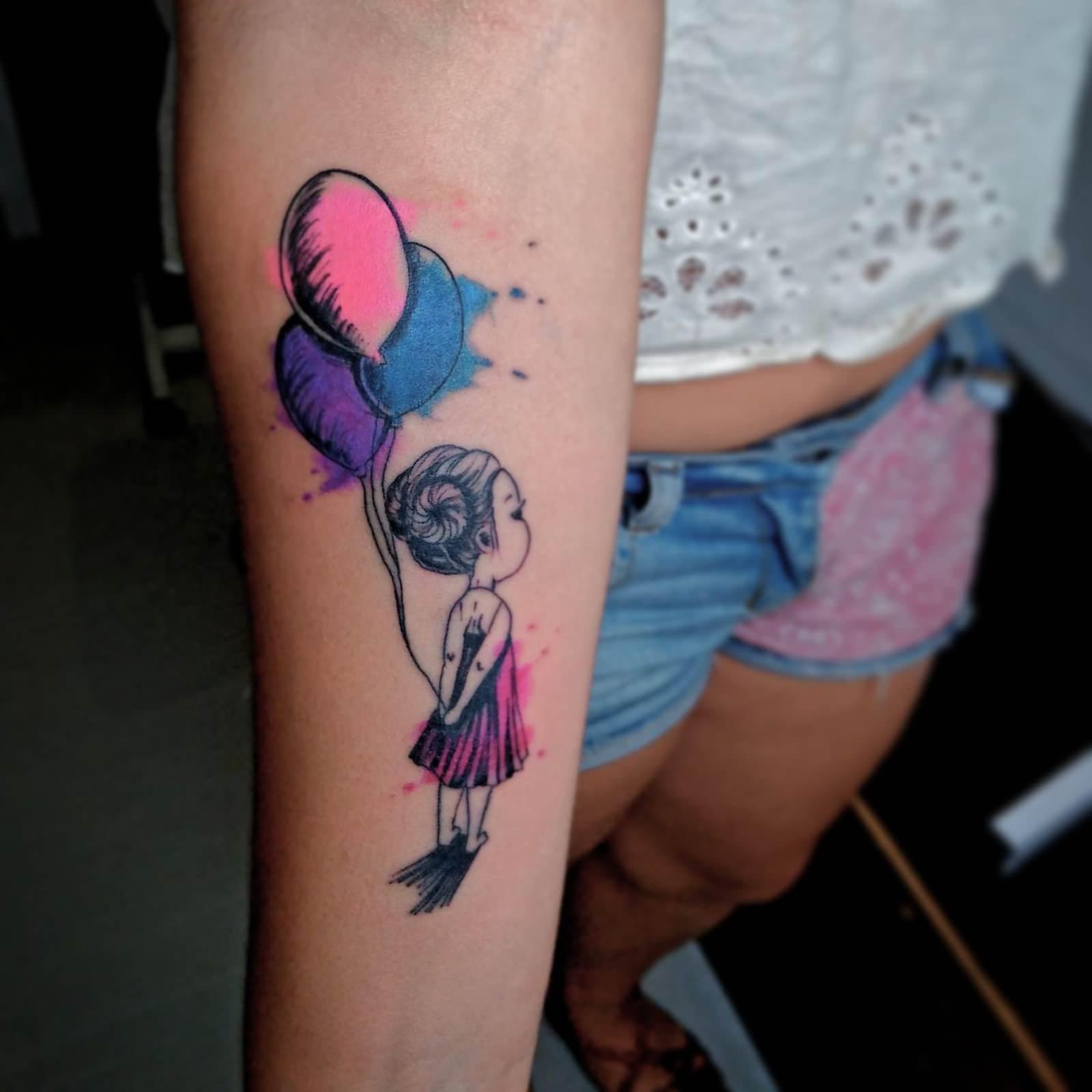 Garotinha segurando balão nas costas tatuada no braço