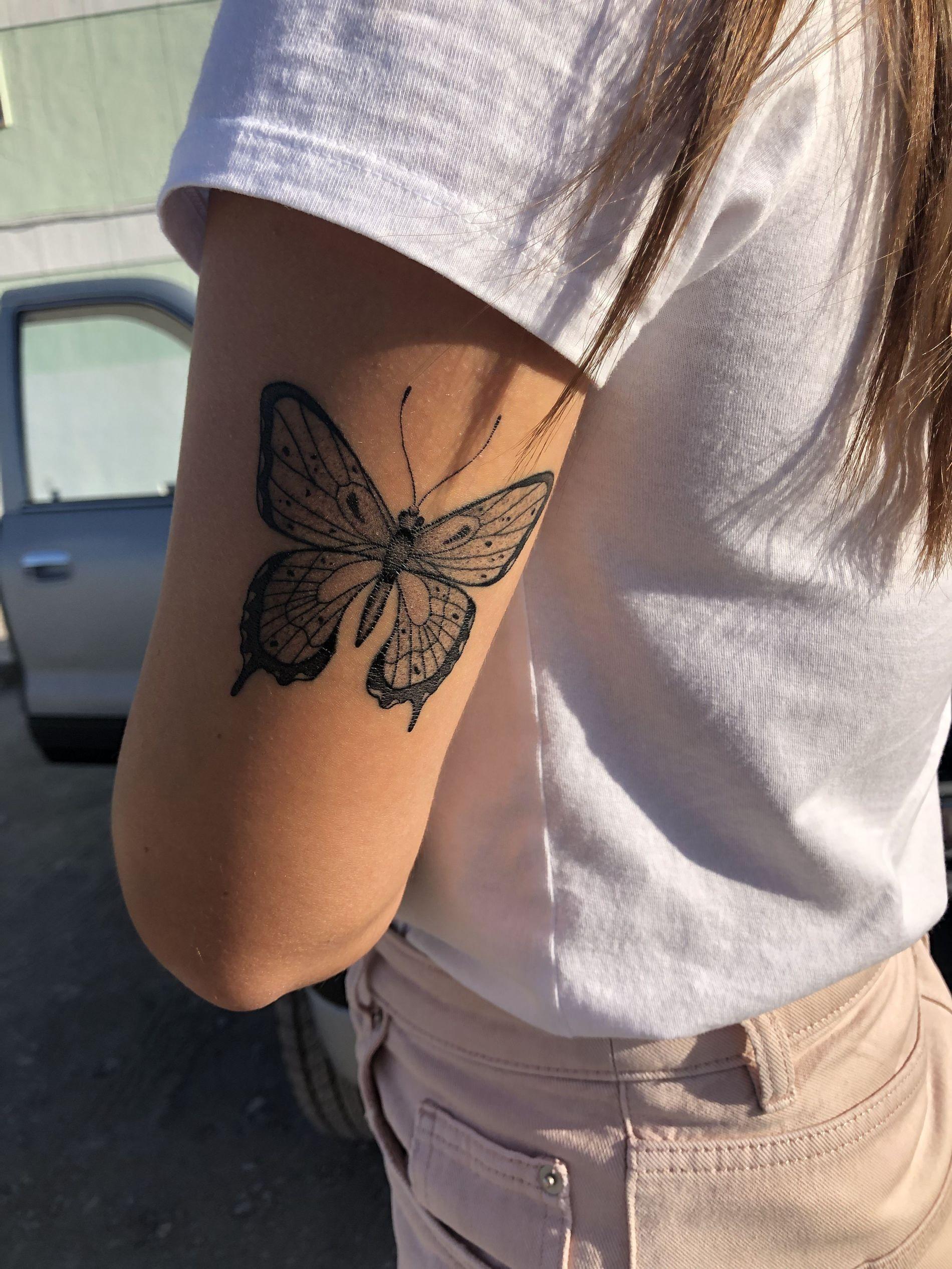 Borboleta preta tatuada atrás do braço