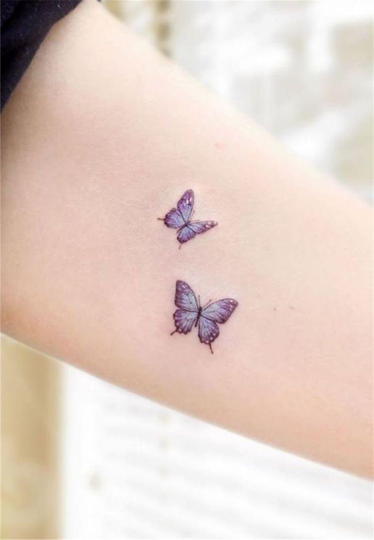 Lindas borboletas em tons lilas tatuadas no braço