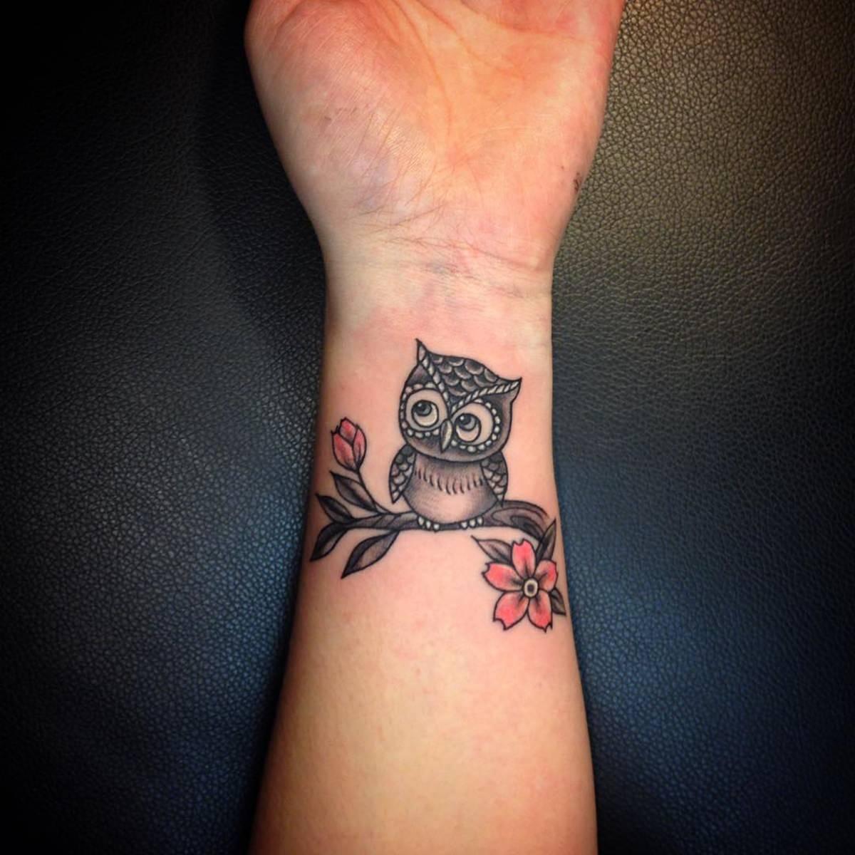 Tatuagem feita no pulso de uma coruja descansando no galho