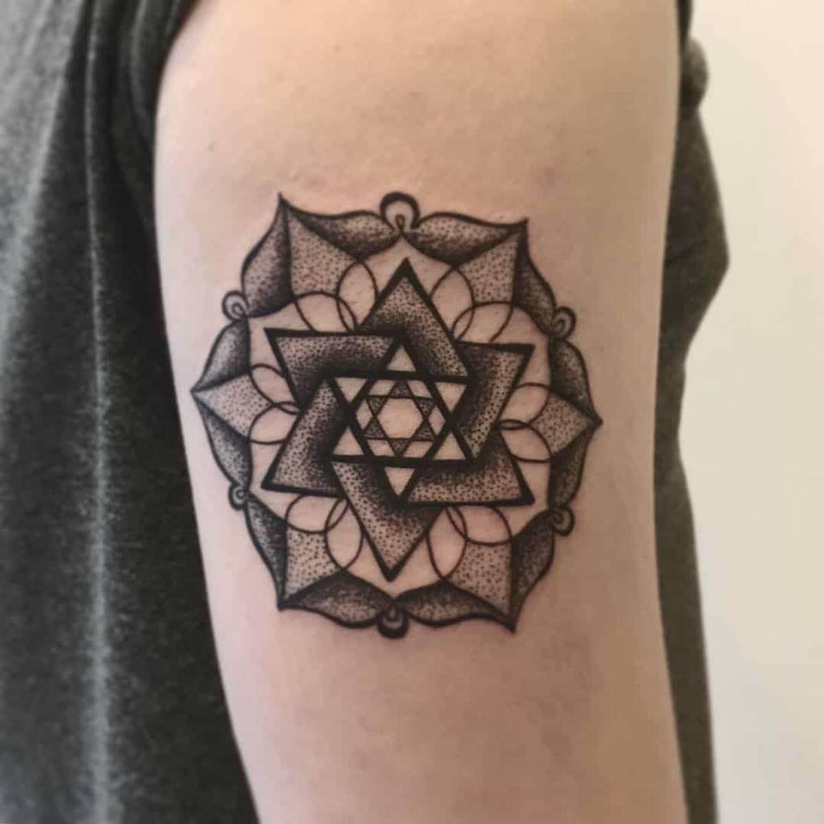 Tatuagem no braço da estrela de Davi dentro da flor de lotus