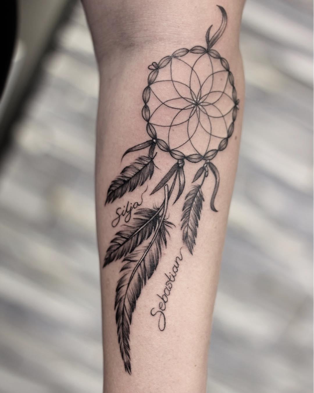 Filtro dos sonhos preto tatuado no braço