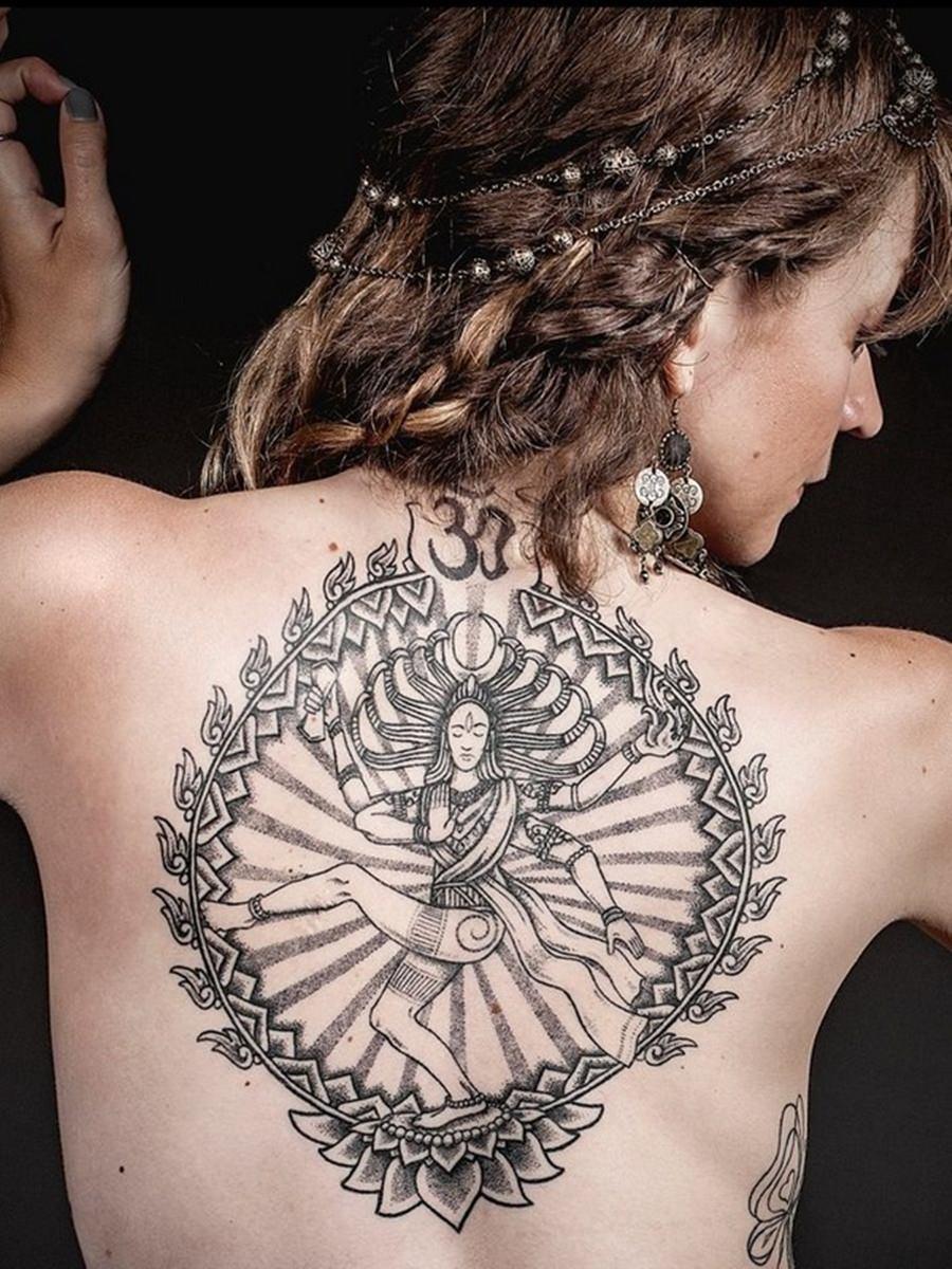 Tatuagem preta nas costas com o desenho da deusa Shiva