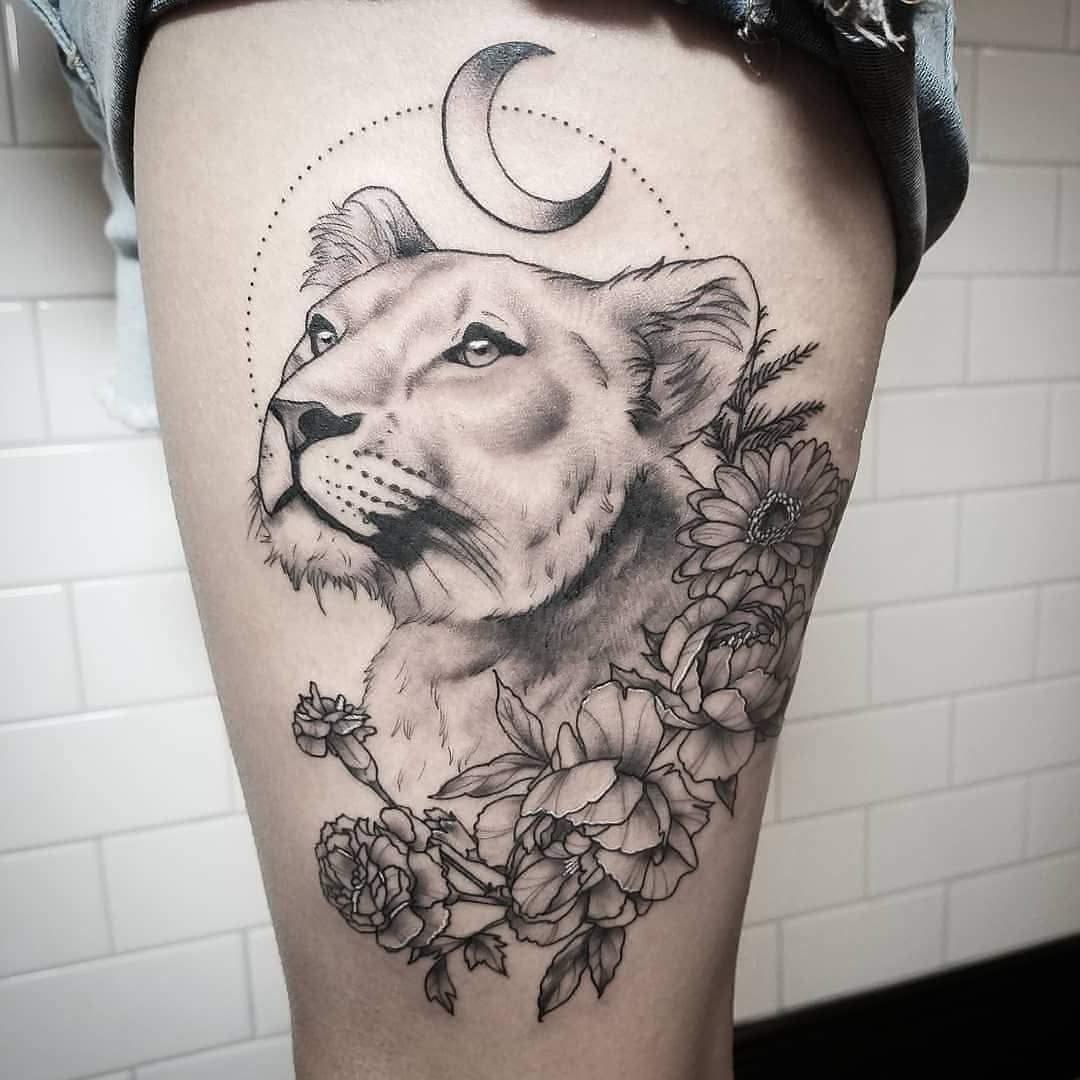 Tatuagem na coxa de uma leoa entre as flores e o luar