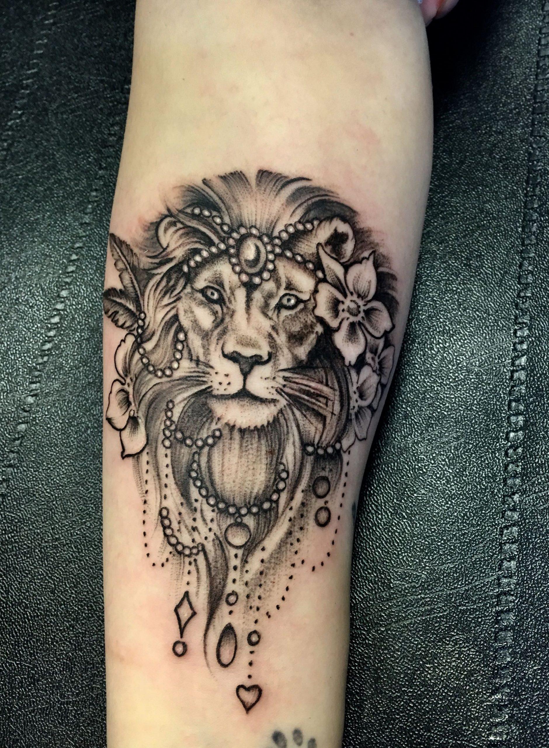 Tatuagem preta no antebraço de uma leão rei