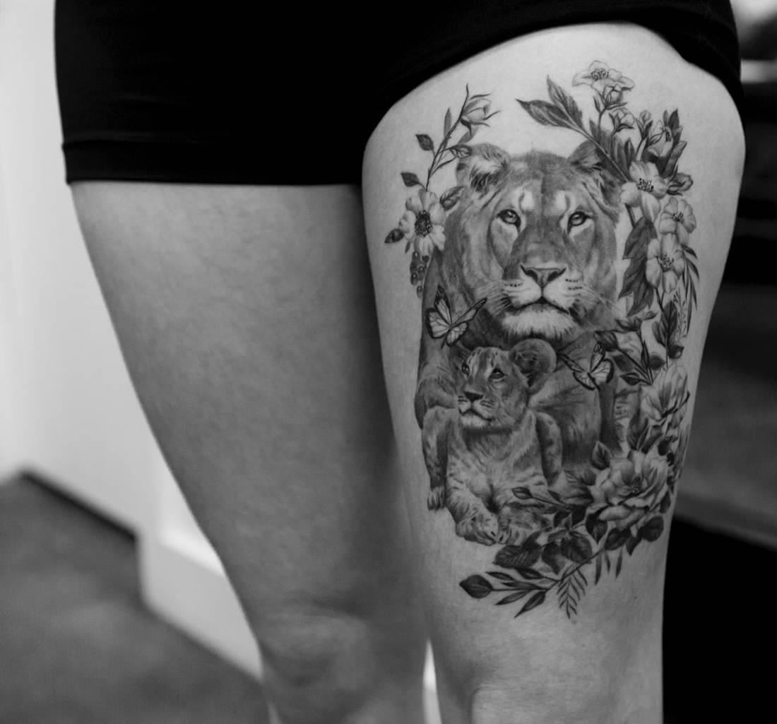Tatuagem na coxa de uma leoa com o seu filhote