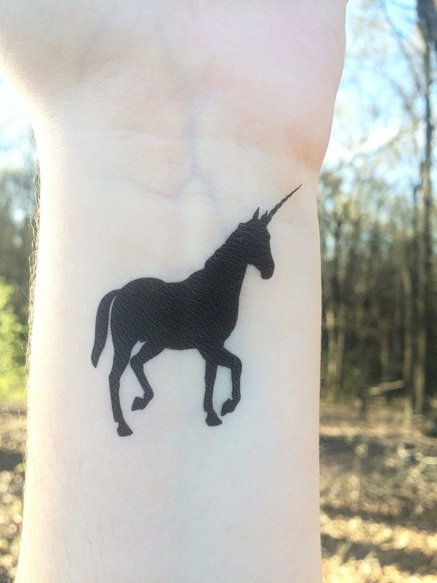 Tattoo de unicórnio preto no pulso