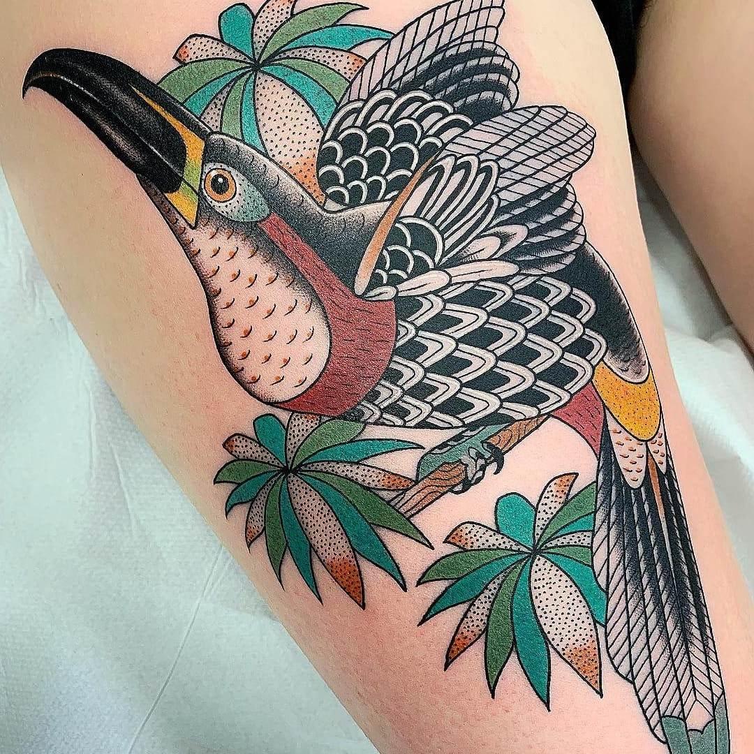 Tatuagem de um tucano na coxa