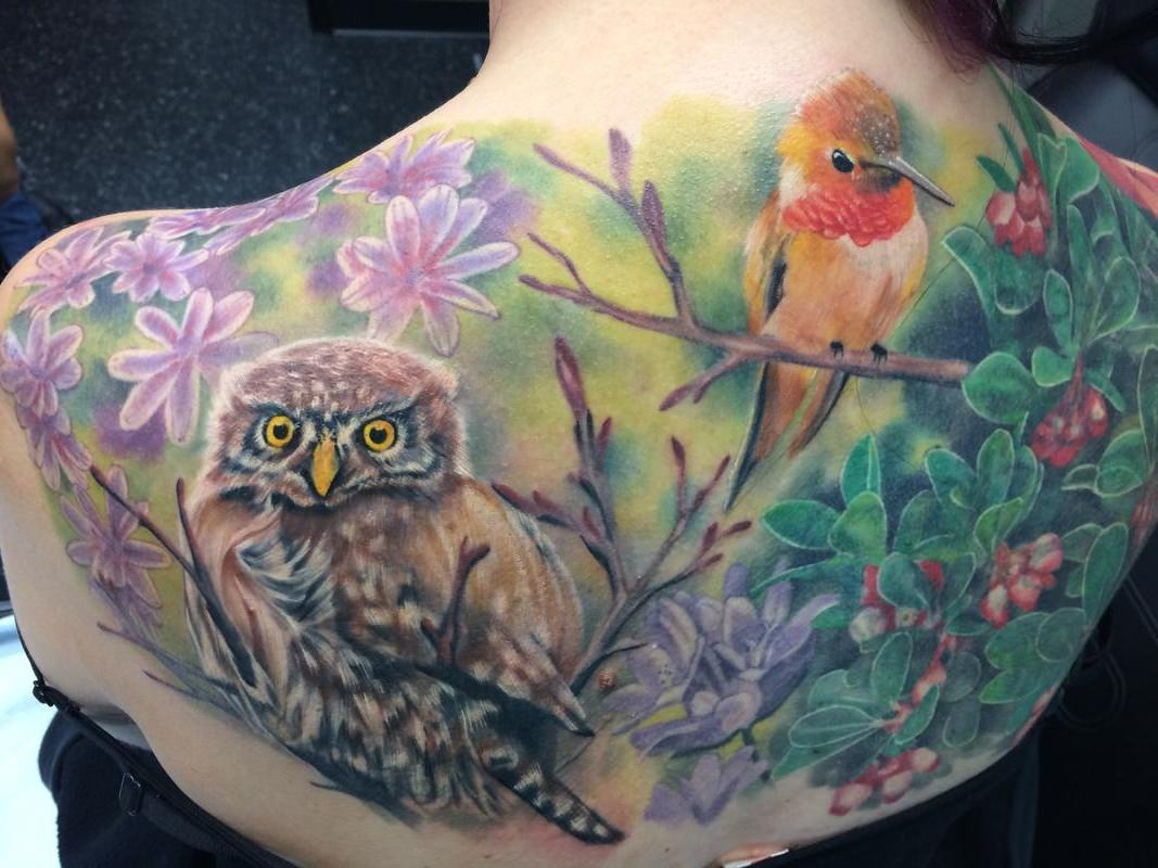Tatuagem grande de aves nos galhos da floresta multicolorida