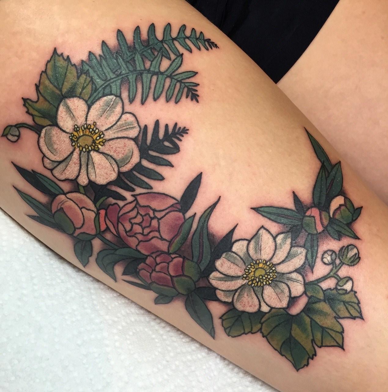 Rosas e flores coloridas tatuadas na coxa
