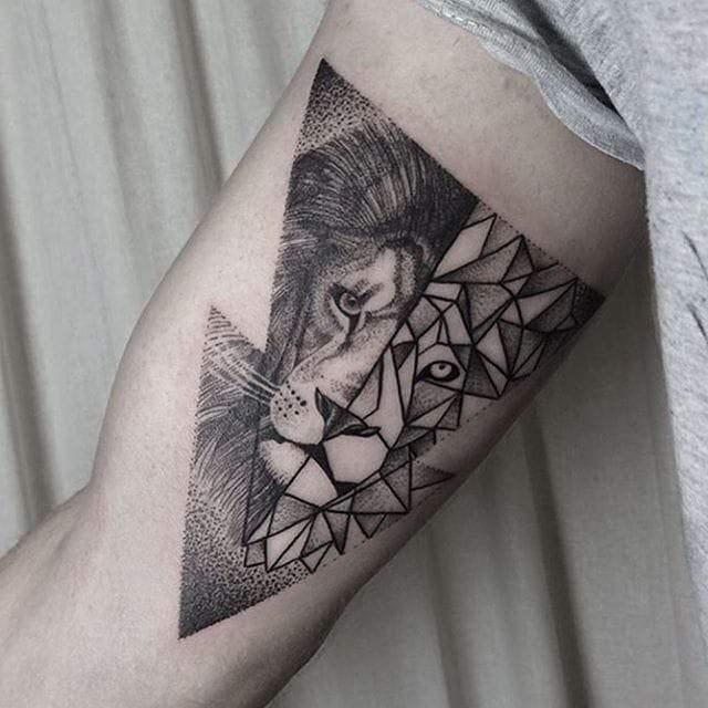 Leão tatuado no braço com efeitos de arabescos