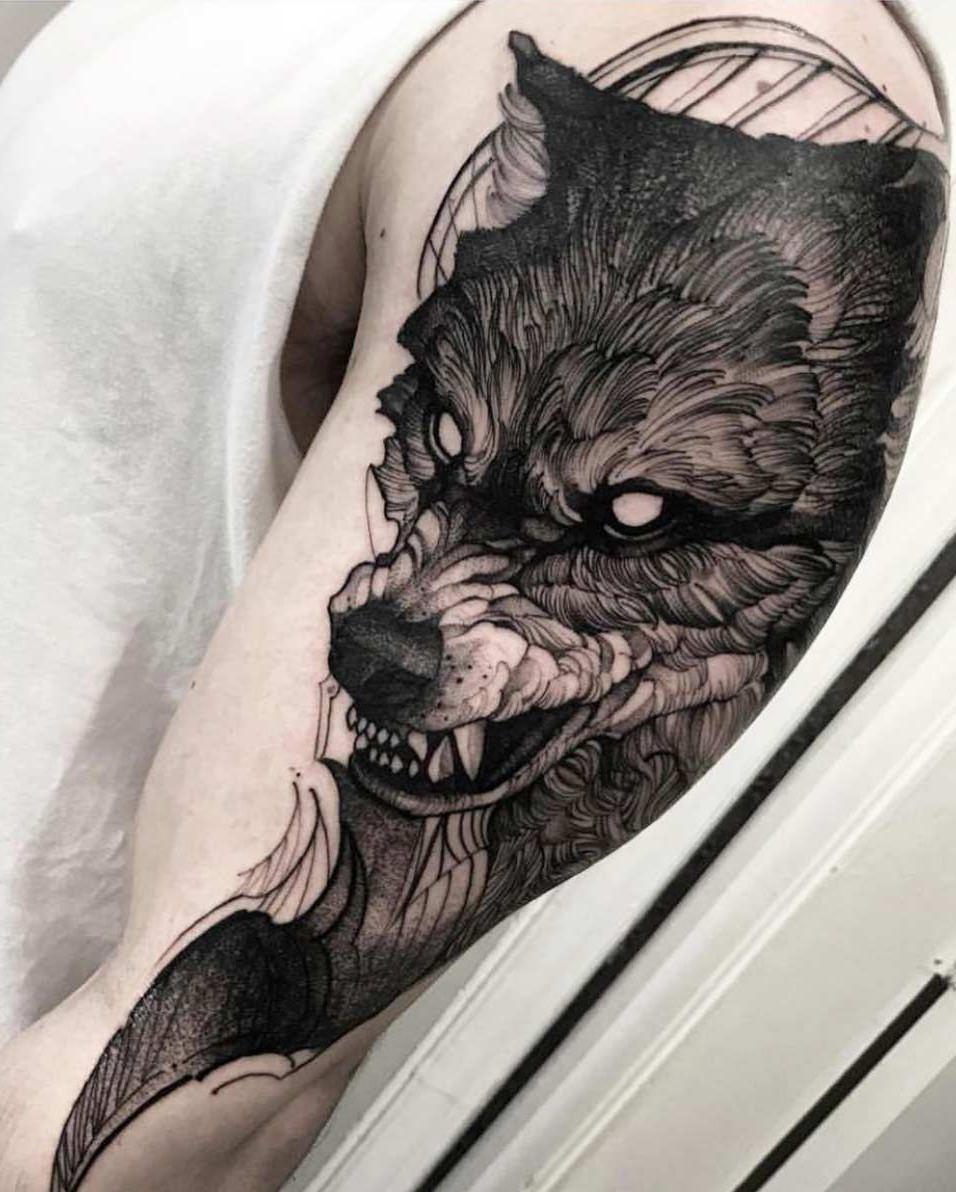 Tatuagem feita no braço de um lobo pronto para o ataque