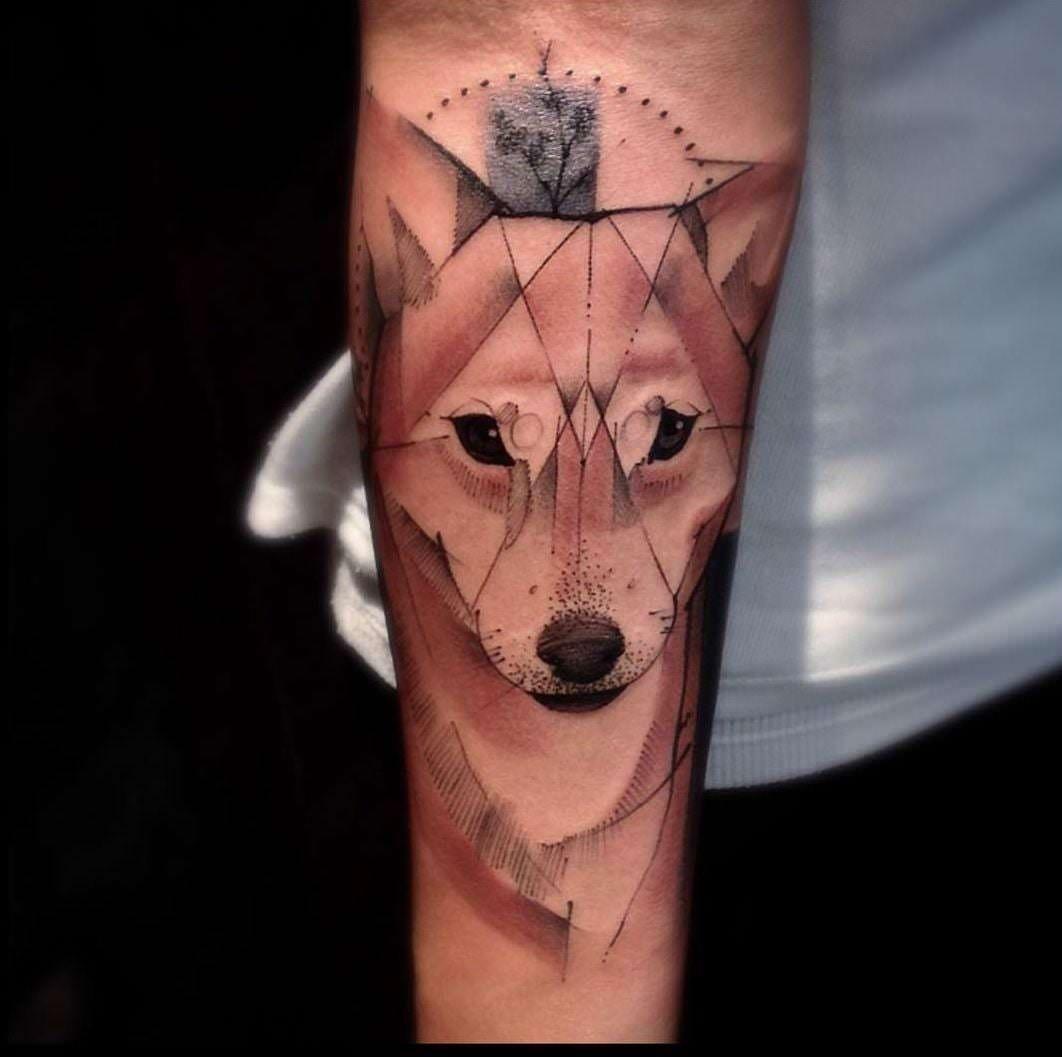Lobo tatuado no braço usando a técnica de cores aquarela