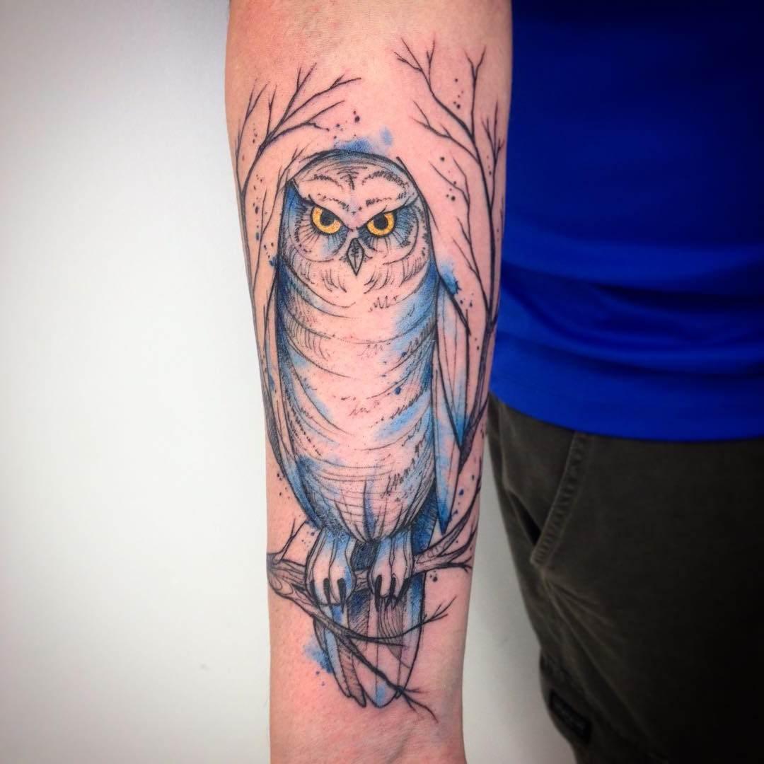 Tatuagem de coruja nas cores aquarela feita no braço