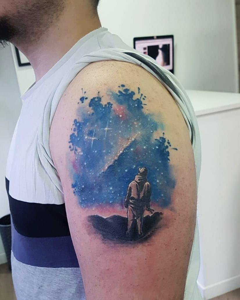 Tatuagem de pessoa olhando para o céu - técnica aquarela