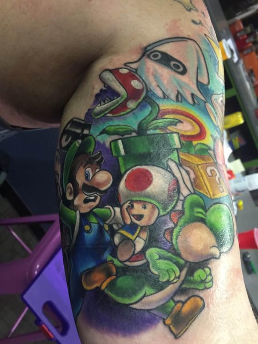 Tatuagem no braço estilo games do Mario: Luigi e Yoshi