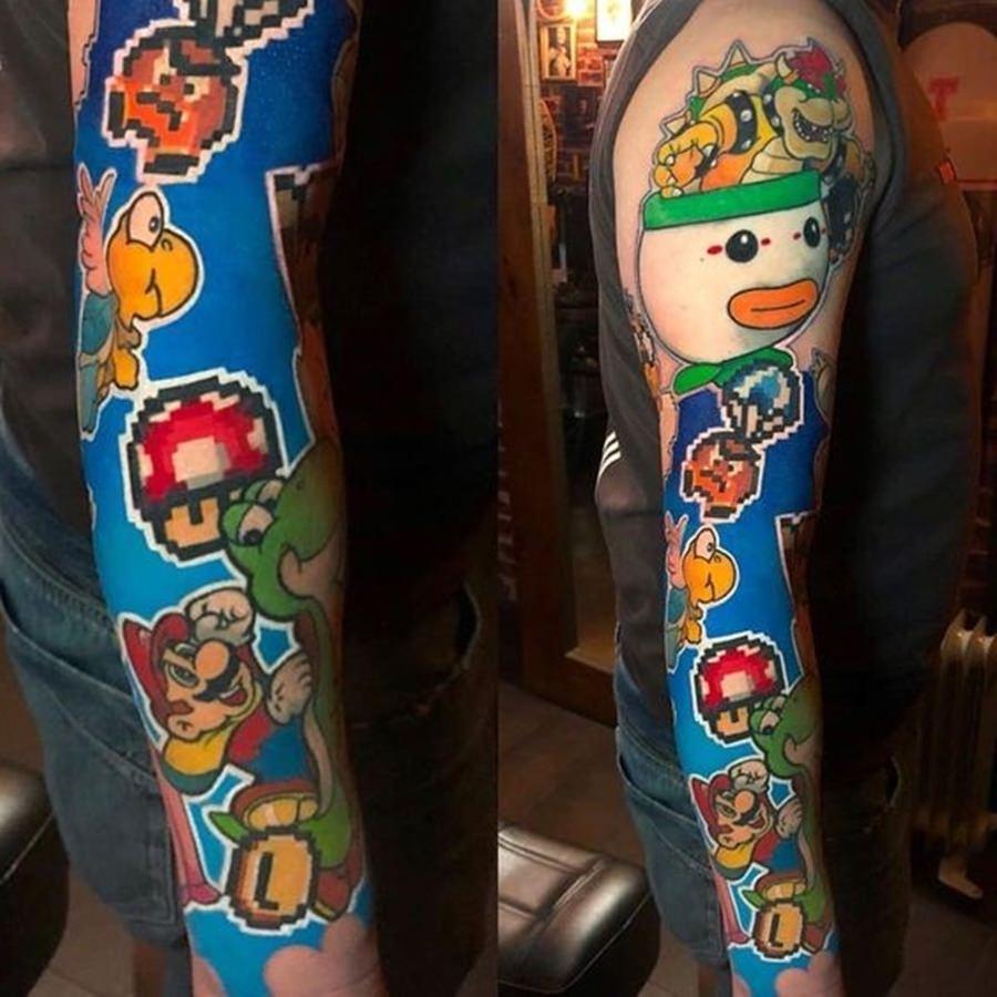 Vários desenhos juntos do game Mario tatuado no braço