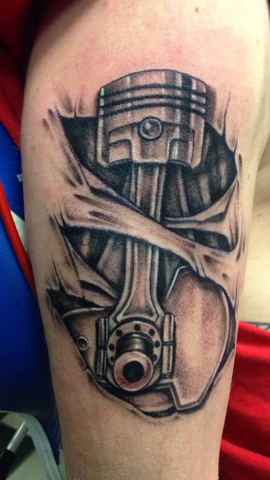 Tatuagem preta de peça de moto no braço