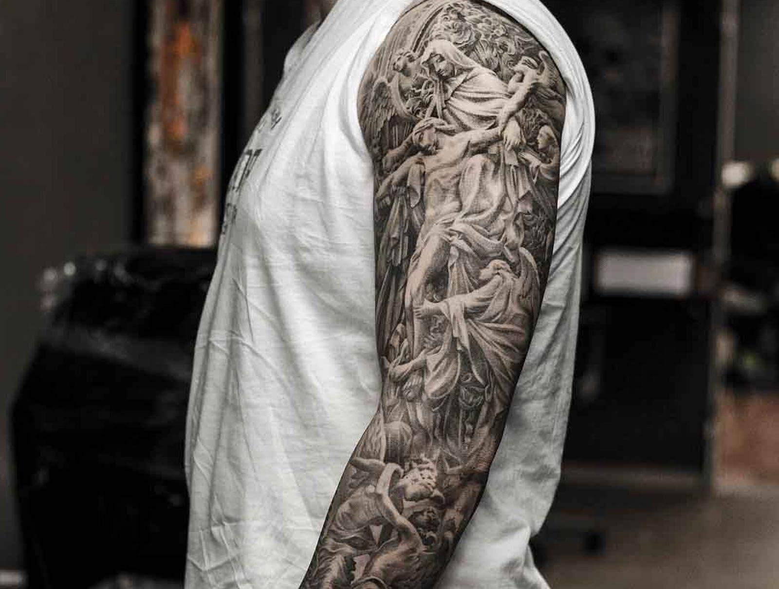 Tatuagem religiosa de Jesus e os anjos feita no braço