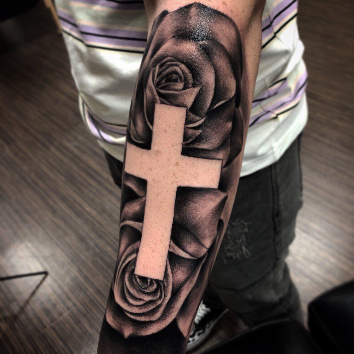 Tatuagem no braço de cruz e rosas